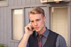 Junger aggressiver Geschäftsmann, der am Telefon spricht Lizenzfreie Stockfotos