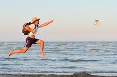 Junger aktiver Mann, der hoch springt und an der Küste läuft Stockfotografie