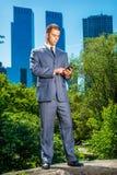 Junger amerikanischer Geschäftsmann, der am Handy, reisend, wor simst Stockbild