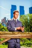 Junger amerikanischer Geschäftsmann, der am Handy, reisend, wor simst Lizenzfreies Stockfoto