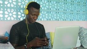 Junger amerikanischer Hippie-Mann des kühlen und attraktiven Schwarzafrikaners mit der Kopfhörervernetzung entspannt mit Handy un stock video