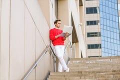Junger amerikanischer Mann, der entfernt an Laptop-Computer arbeitet Lizenzfreies Stockbild