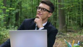 Junger angespornter Geschäftsmann, der im Wald, extrahierender Verstand von den Problemen arbeitet stock video footage