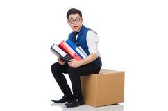 Junger Angestellter, der auf dem Kasten an lokalisiert sitzt Lizenzfreie Stockfotos