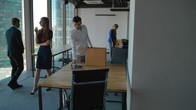 Junger Angestellter, der Kasten mit Doc. und Ausrüstung auspackt Seine Kollegen, die nahe in modernes Büro gehen stock video