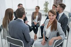 Junger Angestellter im Kreis des gleich gesinnten Geschäftstreffens lizenzfreies stockbild