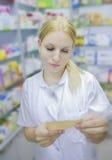 Junger Apotheker, der eine Verordnung betrachtet lizenzfreies stockfoto