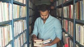 Junger arabischer bärtiger männlicher Student, der Buch zwischen Regalen in der Bibliothek wählt stock video