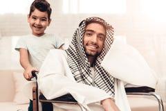 Junger arabischer Mann auf Rollstuhl mit lächelndem Sohn lizenzfreie stockfotografie