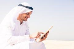 Junger arabischer Mann, der am Strand sitzt Stockfotos