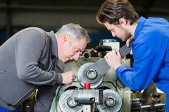 Junger Arbeiter im schützenden Arbeitskleidungsausschnittmetall in der Industrie lizenzfreie stockfotos