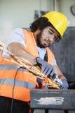 Junger Arbeiter in reibendem Metall der schützenden Arbeitskleidung in der Industrie stockfoto
