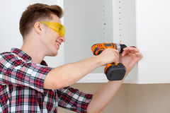 Junger Arbeitnehmer auf dem Zusammenbau von Möbeln lizenzfreies stockfoto