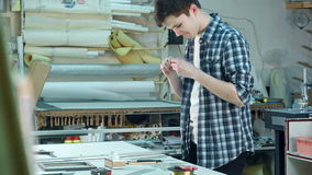 Junger Arbeitnehmer, der das Glas für Rahmen in der Rahmenwerkstatt, seinen Finger plötzlich schneiden schneidet stock video