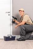 Junger Arbeitnehmer, der eine Tür mit einem schraubenden Bohrgerät installiert Lizenzfreie Stockfotografie