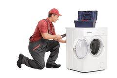 Junger Arbeitnehmer, der eine Waschmaschine repariert Lizenzfreie Stockfotografie
