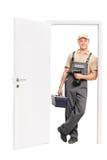 Junger Arbeitnehmer, der einen Werkzeugkasten hält und auf Tür sich lehnt Lizenzfreies Stockfoto