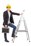 Junger Arbeitnehmer im Sturzhelm mit einem Diplomaten Stockfoto