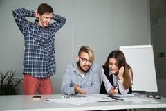 Junger Arbeitnehmer wird durch das Ergebnis der Teamwork überrascht Stockbild