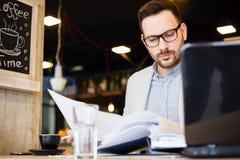 Junger Architekt, der über Bauplänen beim Arbeiten in einem modernen Café schaut lizenzfreie stockbilder