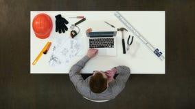 Junger Architekt, der wichtigen Telefonanruf über Zeichnungen hat stock video footage