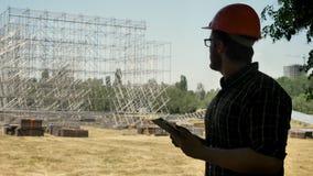 Junger Architekt im Sturzhelm, der neuen Metallbau betrachtet und die Tablette, stehend auf Strohfeld verwendet stock video