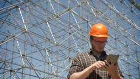 Junger Architekt im Sturzhelm Projekt auf Tablette und Die Stirn runzeln, Metallbau auf dem Hintergrund überprüfend, ernst und stock video footage