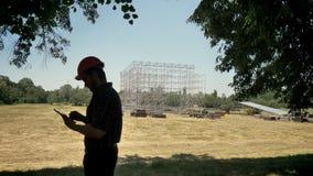 Junger Architekt im Sturzhelm unter Verwendung der Tablette und Betrachten des neuen Metallbaus, planendes neues Projekt stock video
