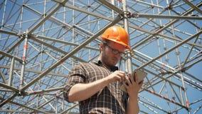 Junger Architekt im Sturzhelm unter Verwendung der Tablette und Betrachten der Metallinstallation auf Hintergrund, der Planung un stock video