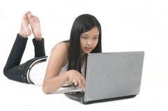 Junger Asiat auf Laptop Lizenzfreie Stockbilder