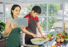 Junger Asiat der Paare Kochen Salat im Küchenraum, das Frauenlächeln, das Menü von der Tablette schaut lizenzfreie stockbilder