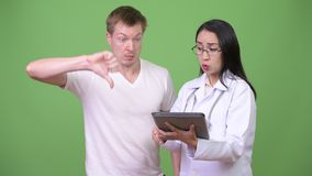 Junger Asiatindoktor, der dem Patienten Beratung des jungen Mannes gibt stock video footage