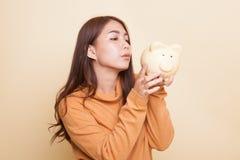 Junger Asiatinkuß eine rosa Münzenbank stockfotos