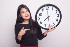 Junger Asiatinpunkt zu einer Uhr stockfotografie