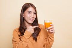 Junger Asiatinpunkt zum Orangensaft lizenzfreie stockfotos