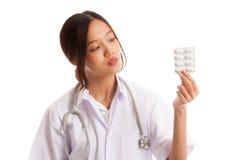 Junger asiatischer Ärztinblick auf Blisterpackung Tabletten Stockfotos