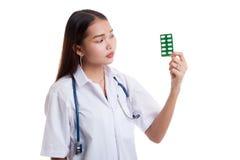 Junger asiatischer Ärztinblick auf Blisterpackung Tabletten Lizenzfreie Stockfotografie