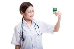 Junger asiatischer Ärztinblick auf Blisterpackung Tabletten Stockbild