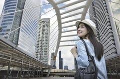 Junger asiatischer Frauenreisender mit einem Rucksack auf ihrer Schulter gehend auf Bahnbrücke über modernem Stadtturm in Bangkok lizenzfreies stockbild