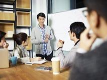 Junger asiatischer Geschäftsmann, der eine Diskussion erleichtert Stockfoto