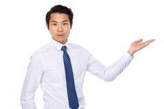 Junger asiatischer Geschäftsmann, der etwas zeigt Stockfotos
