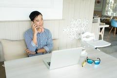 Junger asiatischer Geschäftsmann, der mit Smartphone im Arbeitsplatz arbeitet Cas stockbild