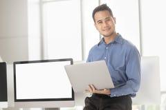 Junger asiatischer Geschäftsmann lächelt erfolgreich im modernen Büroesprit lizenzfreies stockfoto