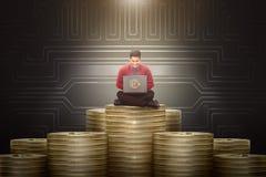 Junger asiatischer Geschäftsmann unter Verwendung des Laptops mit goldenem bitcoin Stapel Lizenzfreie Stockfotografie