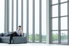 Junger asiatischer Geschäftsmannblick auf die Tablette, die auf glücklichem SMI des Sofas sitzt lizenzfreies stockfoto
