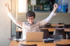 Junger asiatischer glücklicher Student, der seine Hände anhebt stockfotografie