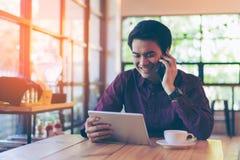 Junger asiatischer hübscher lächelnder Geschäftsmann beim Ablesen seiner Tabelle Stockfoto