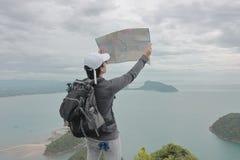 Junger asiatischer Hippie-Mann mit Erforschungskarte der Tasche auf Standpunkt des Berges Reise- und Abenteuerkonzept Stockbilder