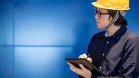 Junger asiatischer Ingenieurmann, der Tablette verwendet lizenzfreies stockbild
