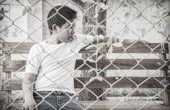 Junger asiatischer Junge, der allein im Park sitzt Stockbilder